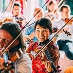 Teambuilding oefening waar alle colega's op een viool spelen