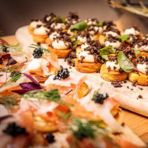 prachtig gedresseerde hapjes gepresenteerd op een houten plankje voor een catering event van KonseptS