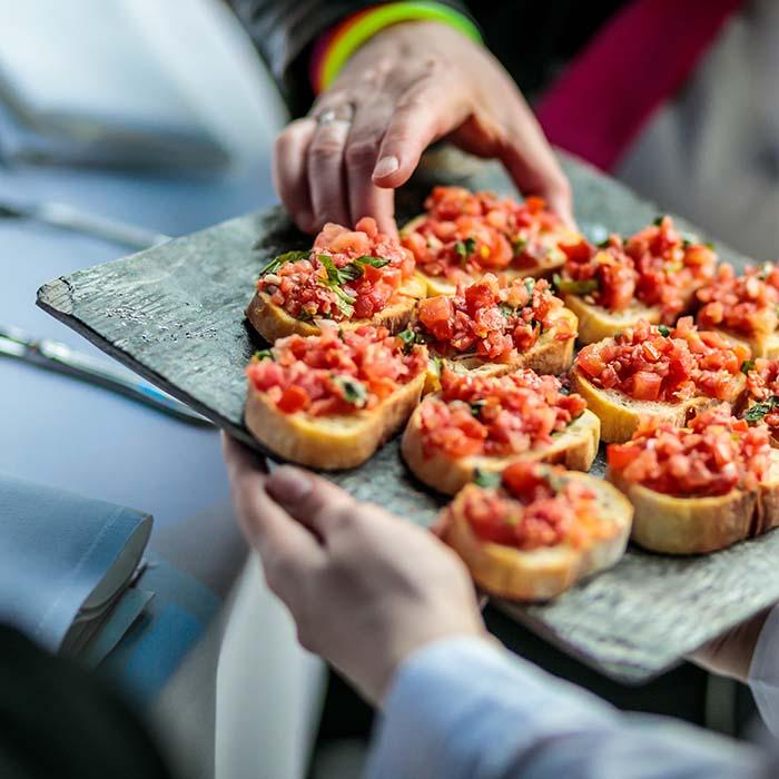 Hapklare geroosterde broodjes belegd met steak tartare geserveerd uit het vuistje op een evenement van SKF
